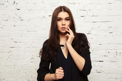 Young fashion woman in black jacket next to brick wall Stock Images