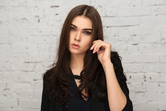 Young fashion woman in black jacket next to brick wall Stock Photo