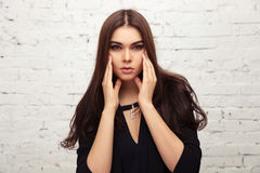 Young fashion woman in black jacket next to brick wall Royalty Free Stock Photography