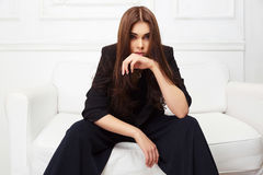 Young fashion woman in black jacket sitting on sofa Stock Photography