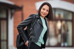 Young fashion woman in black leather jacket walking in city street Royalty Free Stock Image