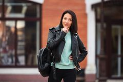 Young fashion woman in black leather jacket walking in city street Royalty Free Stock Photos