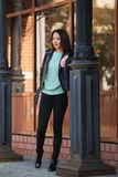 Young fashion woman in black leather jacket walking in city street Royalty Free Stock Images