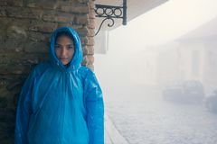 Young fashion woman in blue raincoat standing in mist outdoors. Brick wall of the old house. Pavers. A drizzle of rain stock images
