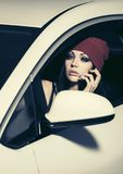 Young fashion woman calling on cell phone driving a car Royalty Free Stock Photo