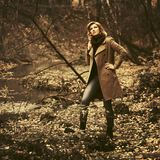 Young fashion woman in classic beige coat walking in autumn forest royalty free stock images