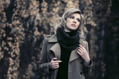 Young fashion woman in beige coat walking in autumn forest Stock Photography