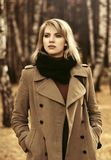 Young fashion woman in classic beige coat walking in autumn park Royalty Free Stock Photos