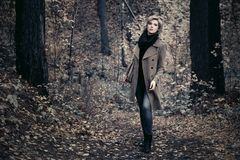 Young fashion woman in classic coat walking in autumn forest Stock Photos