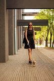 Young fashion woman, walking her dog in the street Stock Photography