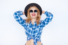 Young fashion woman dressed in a plaid blue shirt and black hat Royalty Free Stock Photos