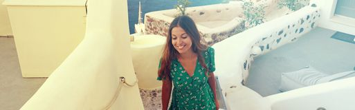 Young fashion woman with green dress walking in Oia resort, Sant stock image