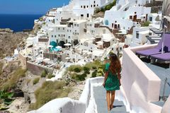 Young fashion woman with green dress and walking on stairs in Oia, Santorini. Female travel tourist on her summer vacations. In Greece stock photography