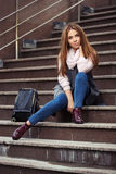 Young fashion woman in grey coat with handbag sitting on steps Royalty Free Stock Photo