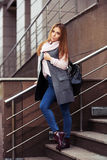 Young fashion woman in grey coat with handbag on steps Royalty Free Stock Photos