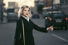 Young fashion woman hailing a taxi cab in city street. Young fashion woman in classic black coat hailing a taxi cab in city street Royalty Free Stock Image