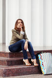 Young fashion woman with handbag sitting on mall steps Royalty Free Stock Photo