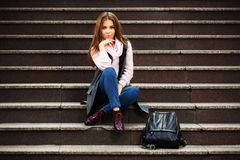 Young fashion woman with handbag sitting on steps. Young fashion woman in grey coat with handbag sitting on the steps Royalty Free Stock Photos