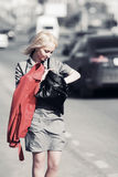 Young fashion woman with handbag walking on a city street Stock Photography