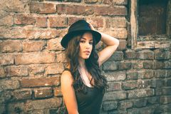 Young fashion woman with hat stand in front old abandoned house. Summer day in the city royalty free stock photography