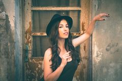 Young fashion woman with hat stand in front old abandoned house. Summer day in the city royalty free stock image