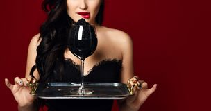 Young fashion woman hold delicacy sturgeon black caviar from hand on red. Young fashion woman hold delicacy sturgeon black caviar in hand on red background royalty free stock image