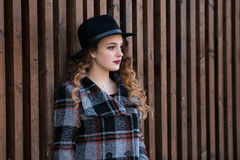 Young fashion woman leaning on a wooden wall Royalty Free Stock Photos