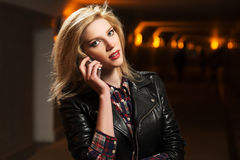 Young fashion woman in leather jacket calling on cell phone Royalty Free Stock Photography