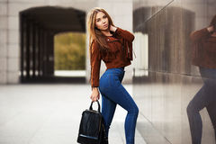 Young fashion woman in leather jacket with handbag stock images