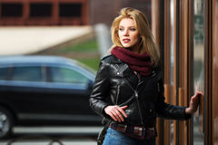 Young fashion woman in leather jacket at the mall door. Young fashion blond woman in leather jacket at the mall door Royalty Free Stock Image