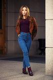 Young fashion woman in leather jacket walking on city street Royalty Free Stock Images