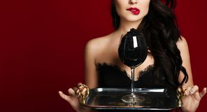 Young fashion woman lick eat sturgeon black caviar from hand on red. Background royalty free stock photography