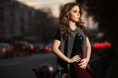 Young fashion woman with long curly hairs on night city street Royalty Free Stock Images