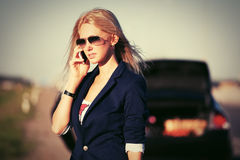 Young fashion woman next to broken car calling on cell phone Royalty Free Stock Photo