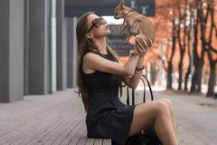 Young fashion woman, playingwith her dog in the park Royalty Free Stock Photo