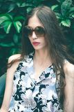 Young fashion woman portrait with sunglasses in garden royalty free stock photo