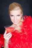 Young fashion woman posing in studio in a red boa Stock Image