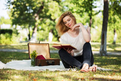 Young fashion woman reading a book in the park Stock Photography