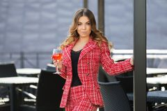 Young fashion woman in red tweed jacket and shorts suit at sidewalk cafe. Young fashion woman with glass of wine at sidewalk cafe Stylish female model in red Stock Images
