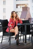 Young fashion woman in red tweed jacket and shorts suit at sidewalk cafe. Young fashion woman with glass of wine at sidewalk cafe. Stylish female model in red Stock Image
