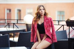 Young fashion woman in red tweed jacket and shorts suit at sidewalk cafe. Young fashion woman sitting on chair at sidewalk cafe. Stylish female model in red Stock Photography