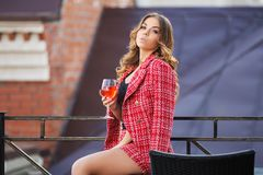 Young fashion woman in red tweed jacket and skirt suit at sidewa. Young fashion woman with glass of wine at sidewalk cafe Stylish female model in red tweed Royalty Free Stock Photography