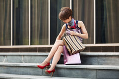 Young fashion woman with shopping bag sitting on mall steps Stock Images