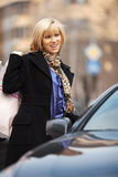 Young fashion woman with shopping bags at the car Royalty Free Stock Photography