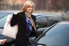 Young fashion woman with shopping bags at the car Stock Image