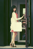 Young fashion woman with shopping bags at the mall doorway Royalty Free Stock Photography