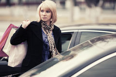 Young fashion woman with shopping bags next to car Royalty Free Stock Images