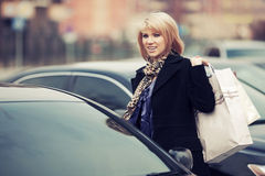 Young fashion woman with shopping bags next to car Royalty Free Stock Photography
