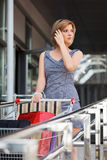 Young fashion woman with shopping cart in the mall Stock Images
