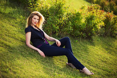 Young fashion woman sitting on the grass outdoor Royalty Free Stock Photography